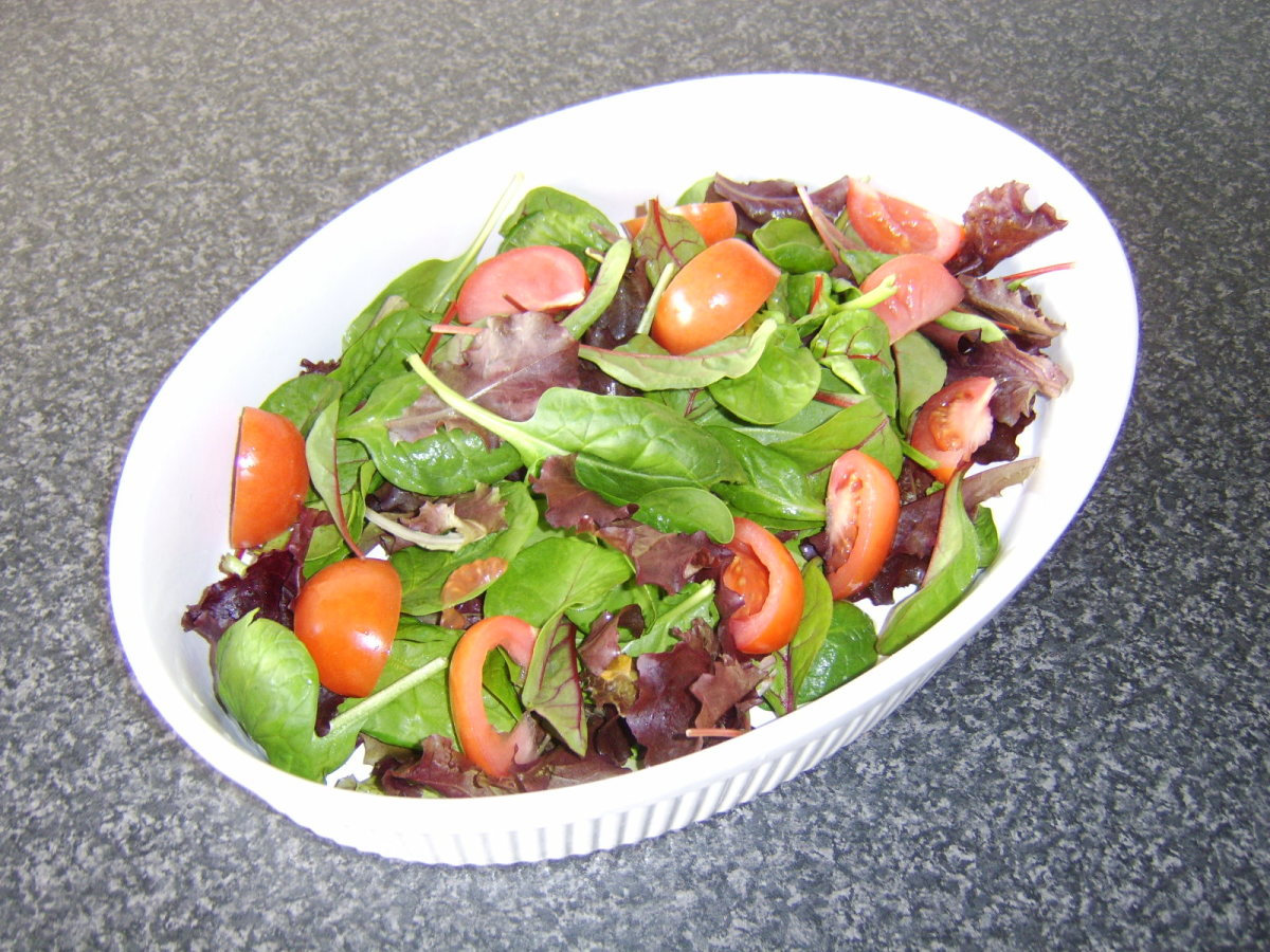 The salad is tossed in a bowl before being added to a serving platter