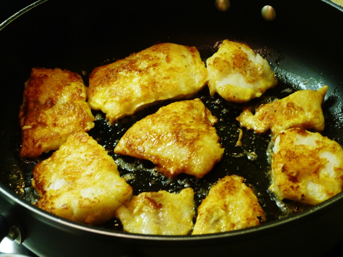 Sauteing the lightly battered fillets of fish in a non-stick skillet on top of the stove.