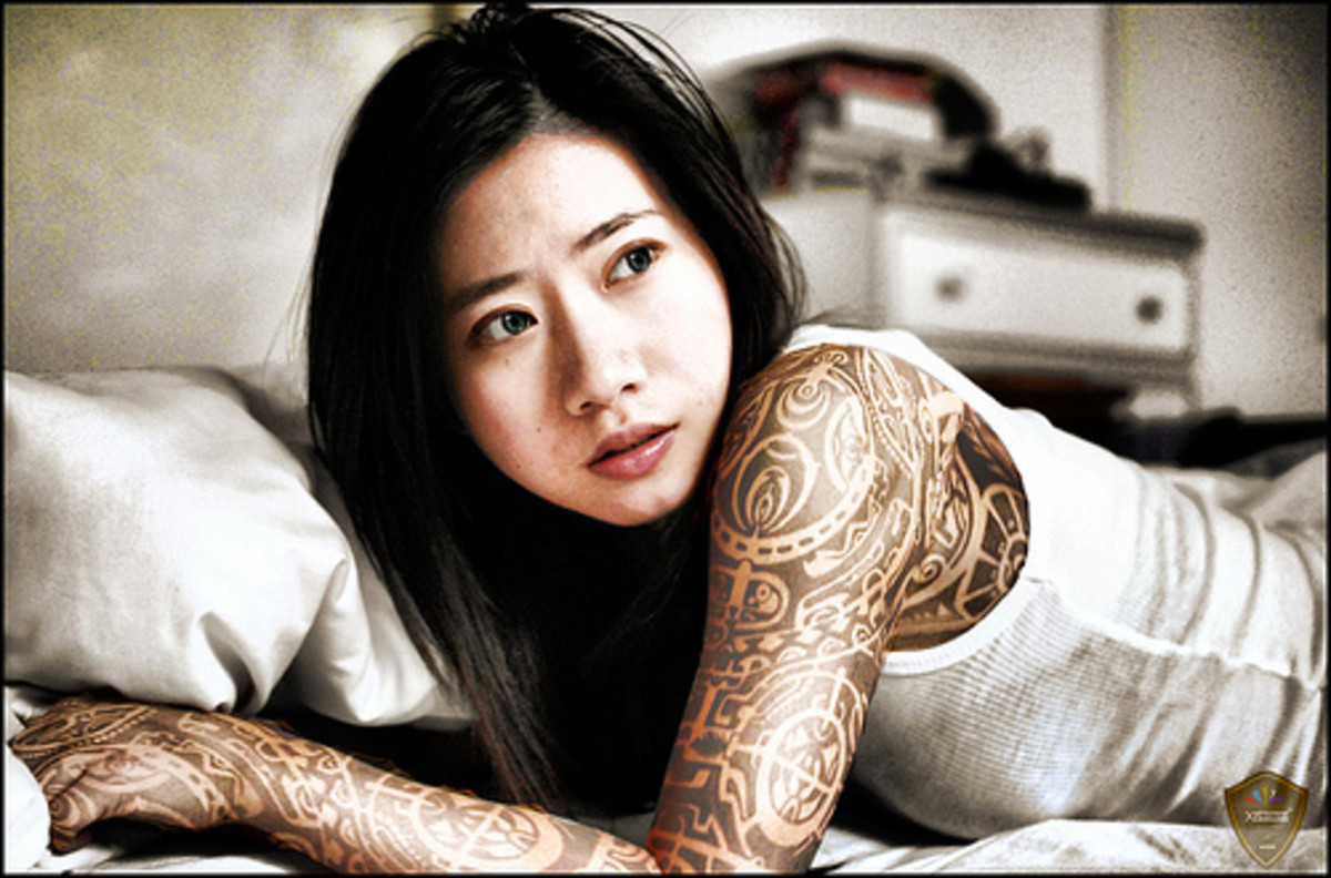 Asian woman with tattooed arm