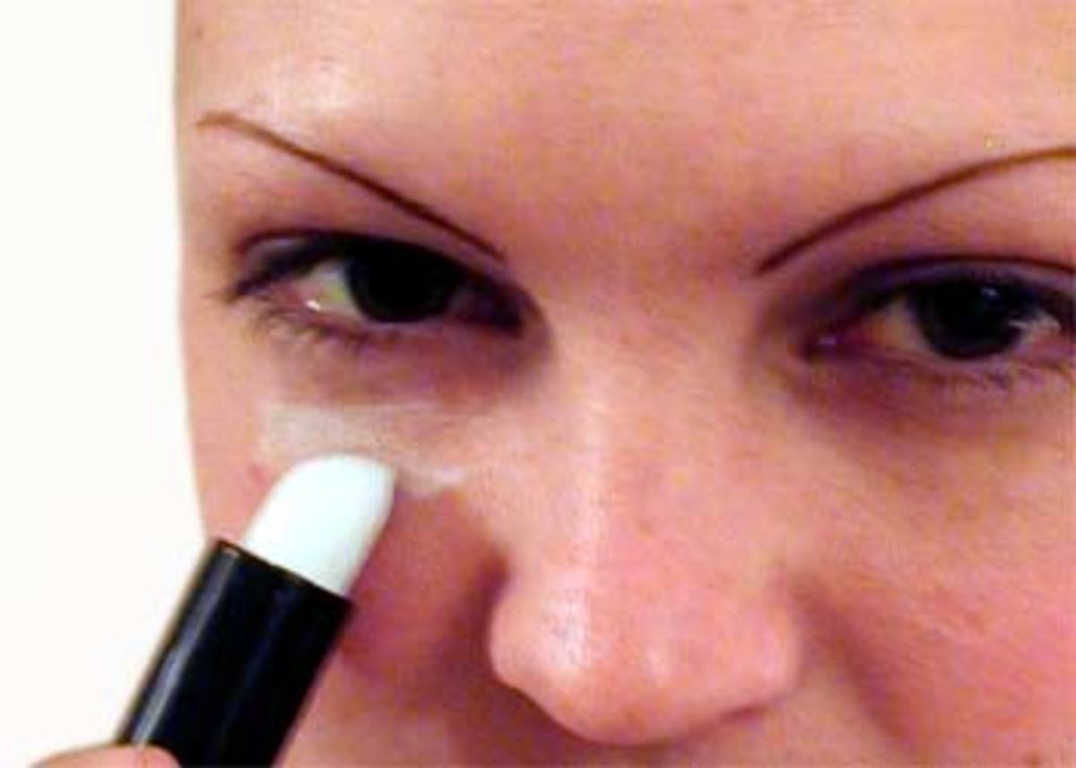 Use a white or green tinted concealer to cover dark under-eye circles. Lightly apply normal make-up over the concealer.