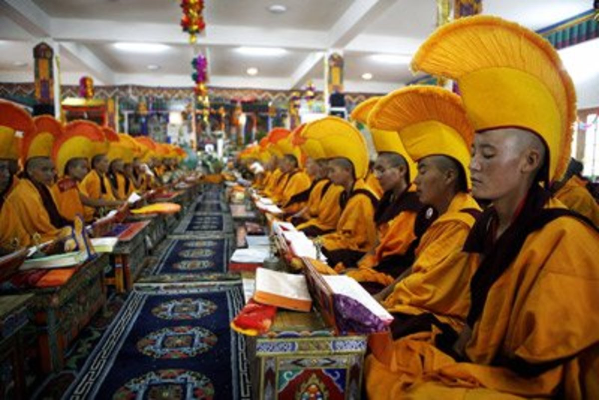 Buddhist nuns pray for their spiritual leader. From article about Buddhism, reincarnation and karma.
