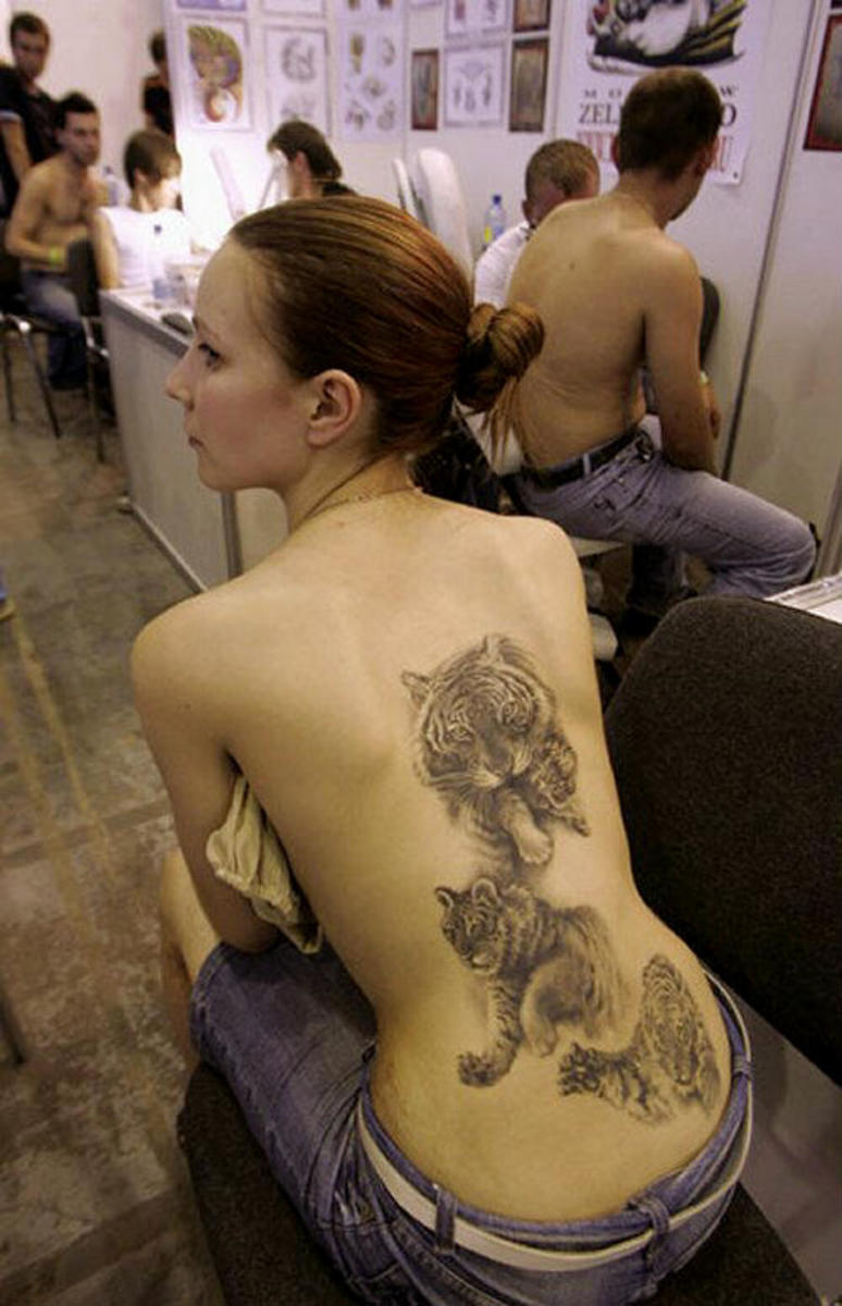 Three tiger tattoos on woman's back