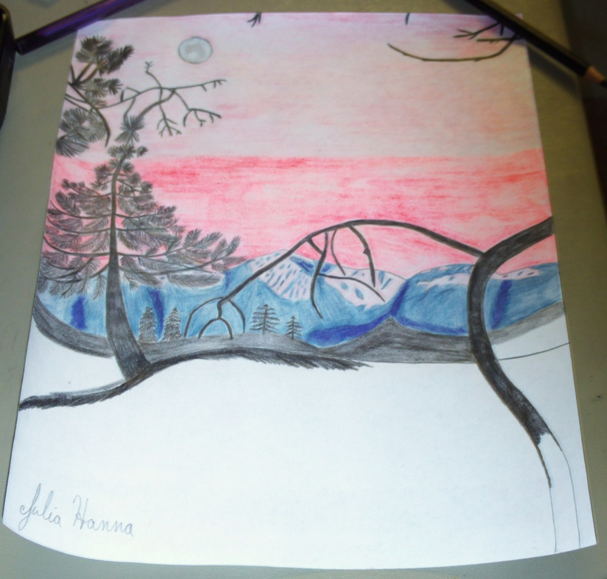 The black colored pencil is being used to created the shape of the mountains in this sunset scene.