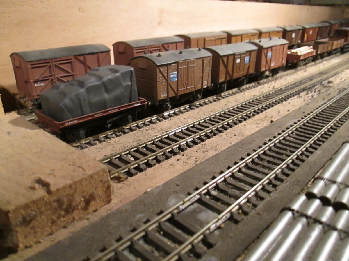Fiddleyard B:on the Thoraldby (cf) layout: A line-up of divers British Railways' and ex-LNER goods and perishables vans (fruit/meat) with a B R low-sided wagon and tarpaulined load this end.