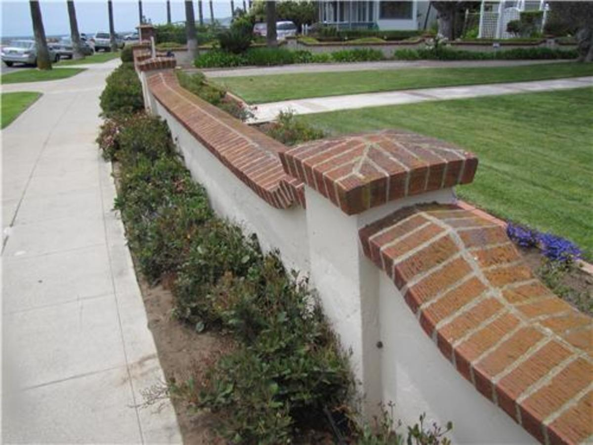 White stucco retaining wall ideal for mediterranean for Stucco garden wall designs