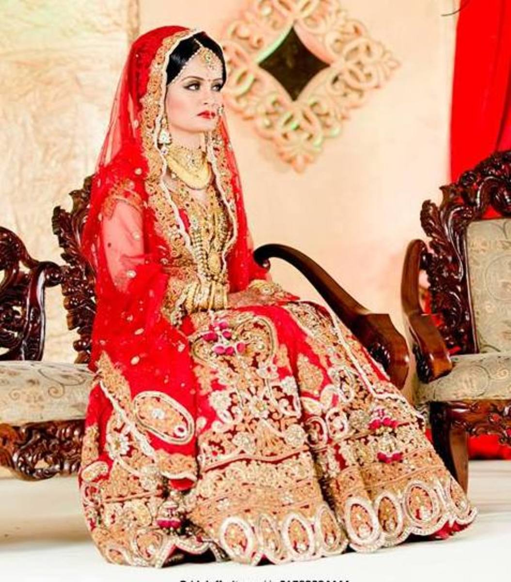 A bride sitting on stage in a red bridal lehenga.