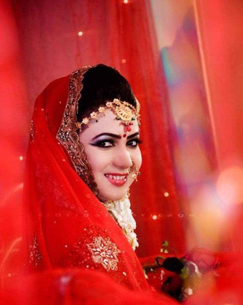 Mischievous smile by a bride in scarlet.