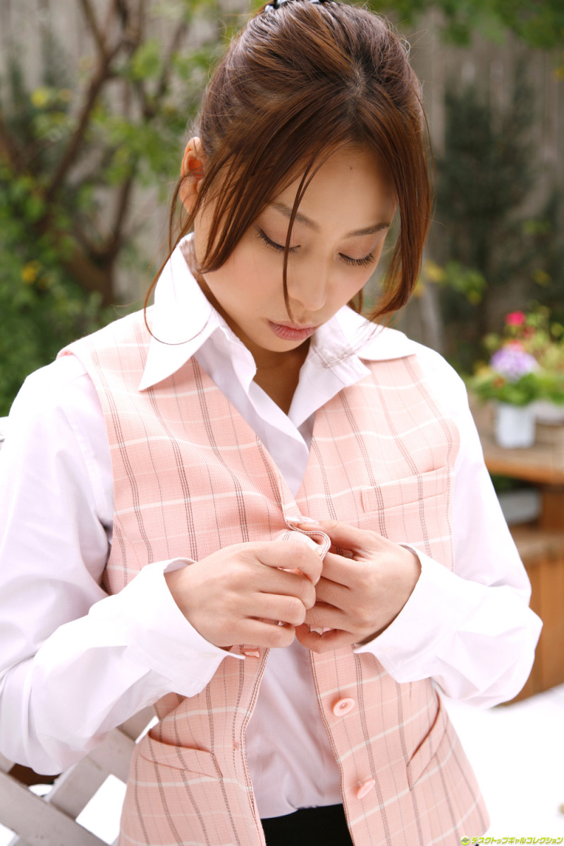 Mika Inagaki trying to button up her vest. She seems very focused.