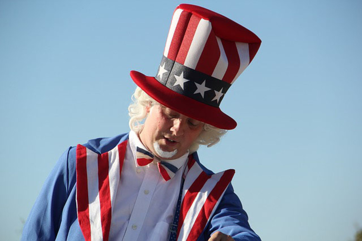 "4th of July American symbol is a man dressed in red,white, and blue- colored suit which is topped off with a tall hat showing the stars and stripes representing the American flag. He is known as ""Uncle Sam""."