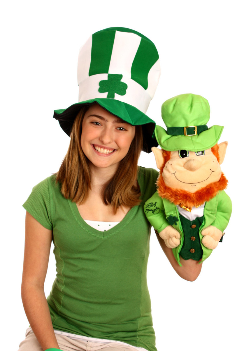 A young girl wearing a top hat with shamrock and holding her puppet Leprechaun..