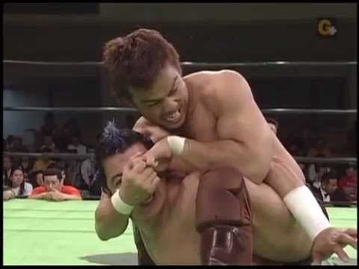 KENTA with a chin lock on Ricky