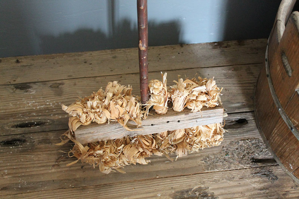 Primitive kitchen broom made of wood with corn stalks as the sweeping head