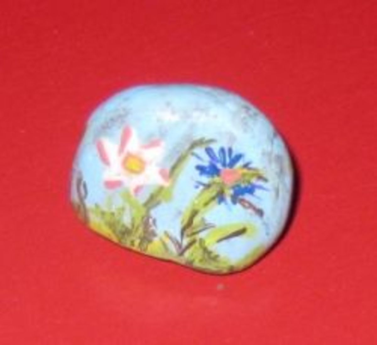 Painted rock with flowers and grass.