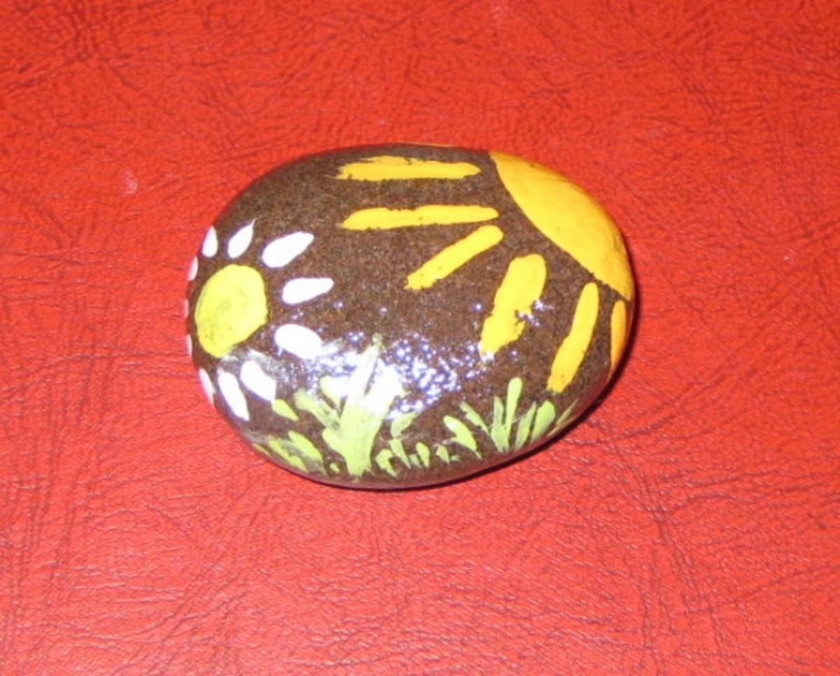Flower, Project No. 4. 2012. I left this rock brown. I usually paint the entire surface of the rock, but this one was pretty as it was. Then I painted the sun, the flower, and some grass. April 2012.