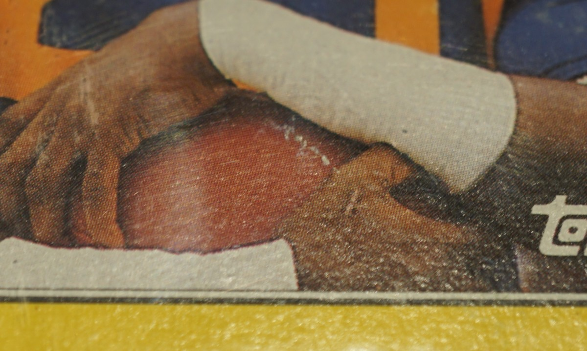 This is a 1987 Topps Box Bottoms of Eric Dickerson. It's graded PSA 3. Although you couldn't tell that by looking at it from afar, one major problem is surface damage. The football has a visible scratch.