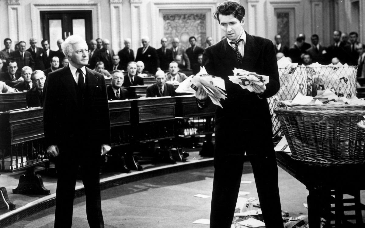 """James Stewart (standing next to Claude Rains - Sen. Paine) with """"Taylor Made"""" letters in  his hands"""