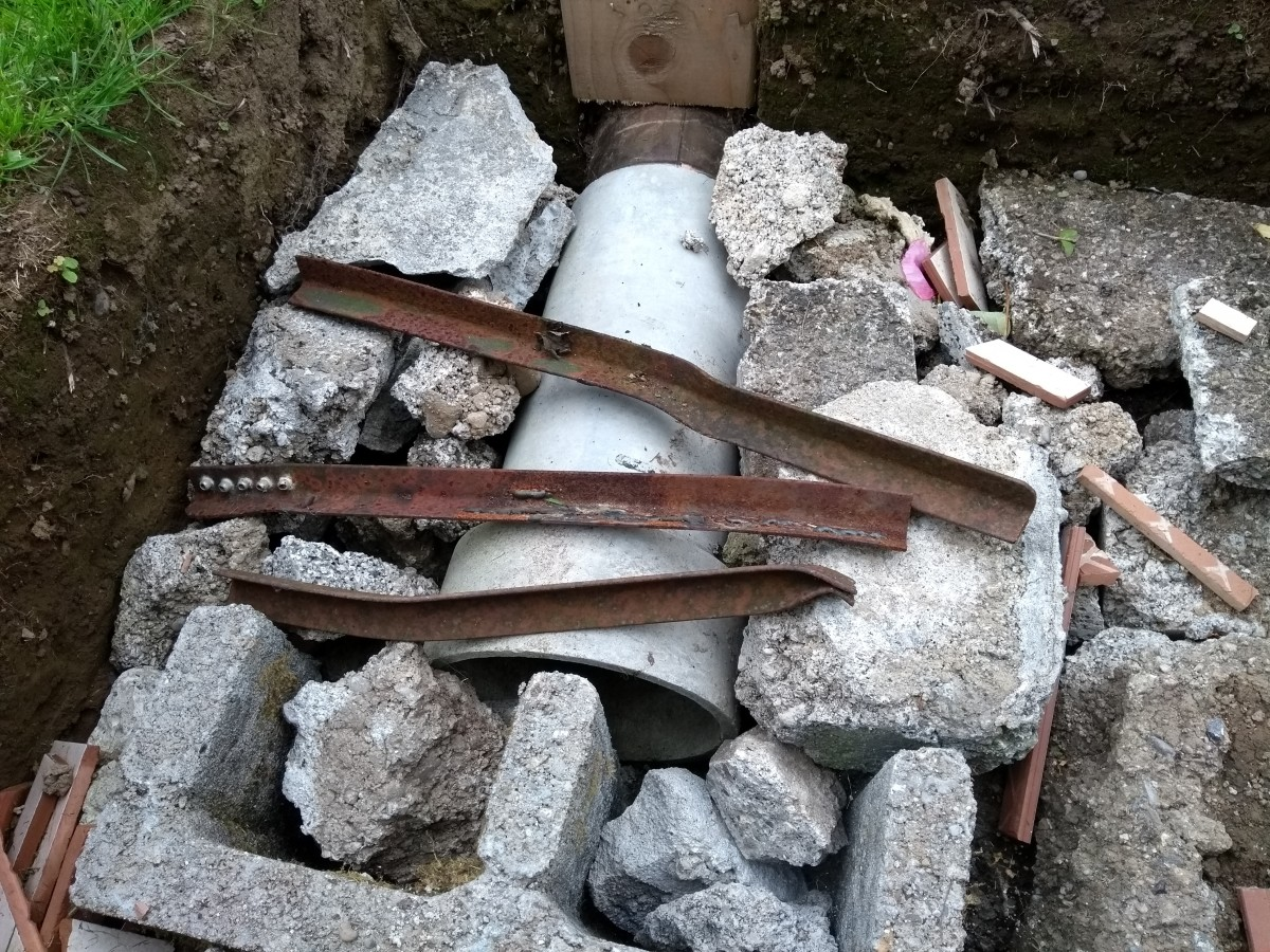 Some recycled angle iron bars protect the concrete pipe from damage.