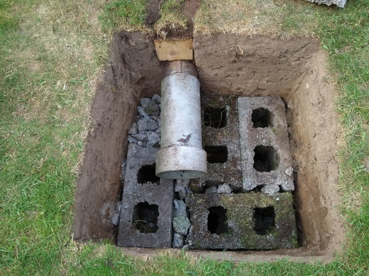 """I used five layers of 9"""" blocks. A piece of waste concrete flue was used to extend the drain into the centre of the hole."""