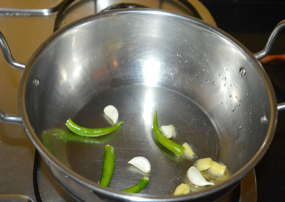 To the same pan, add garlic, broken green chilies, and ginger. Saute for a few seconds.
