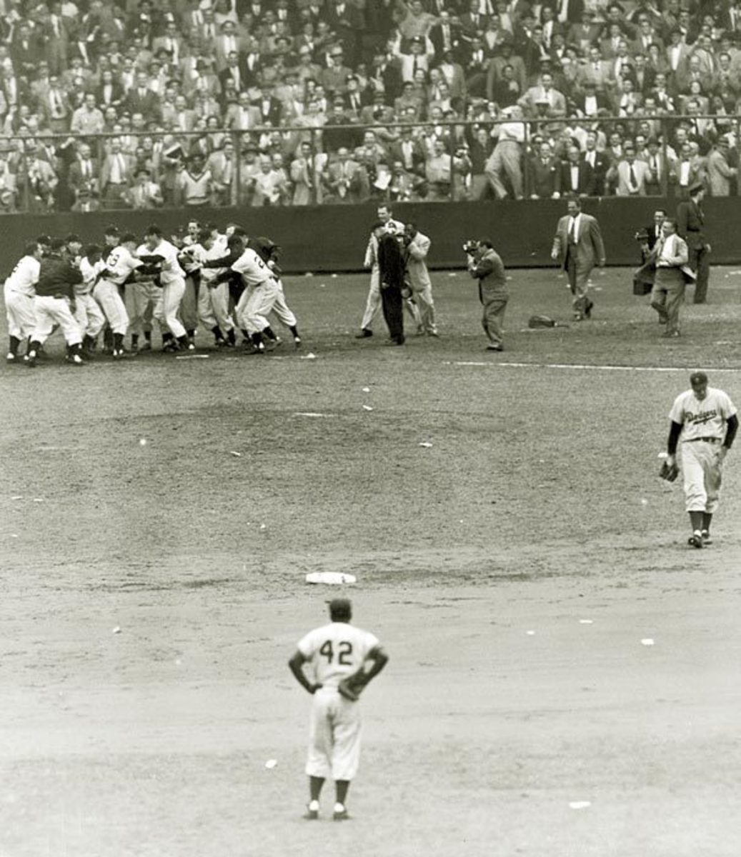A rarely seen angle: The Giants mob Thomson as a dejected Ralph Branca starts the long walk to the visitors' locker room in center-field. Jackie Robinson stands in shock.