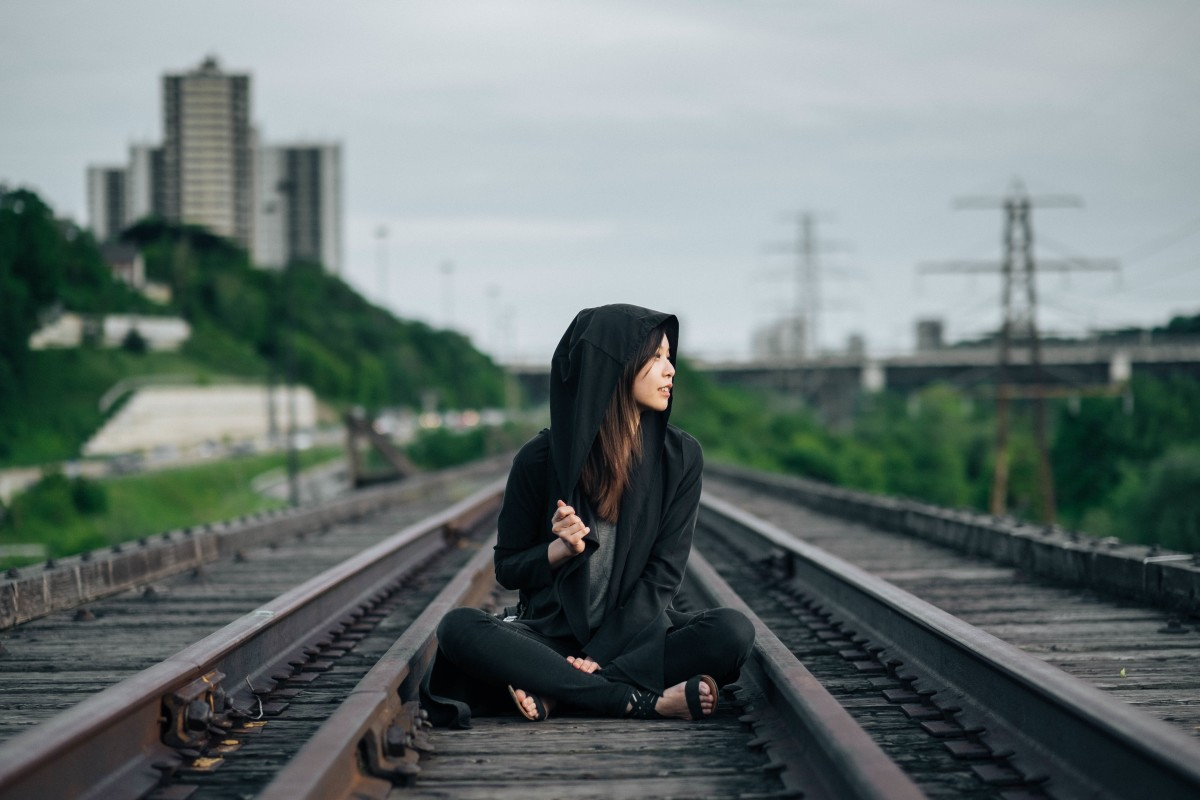 Woman sitting on the train tracks.