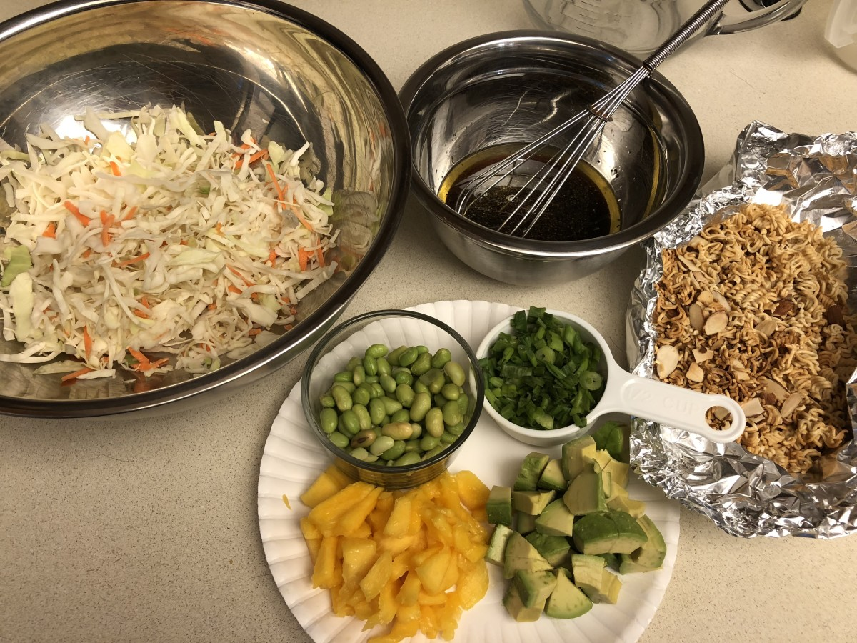 Ingredients assembled- cabbage, dressing, toasted noodles & almonds, green onions, avocado, mango, and edamame