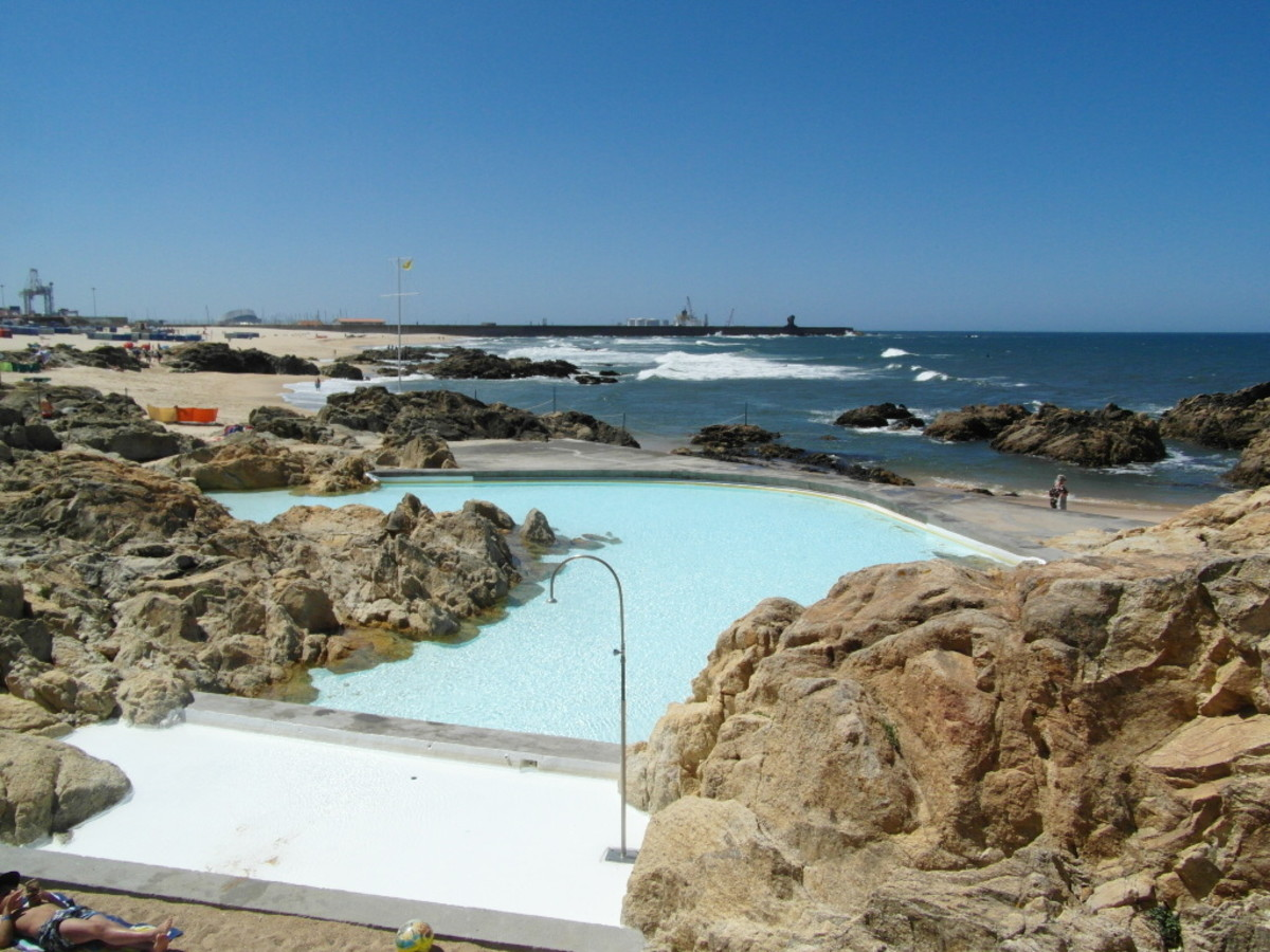 The shallow pool at Piscina das Mares, Leca da Palmeira, with the beach and harbour wall in the background.