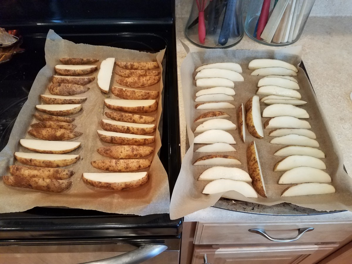 Line two cookie sheets with parchment paper and line the parchment paper with sliced potatoes.