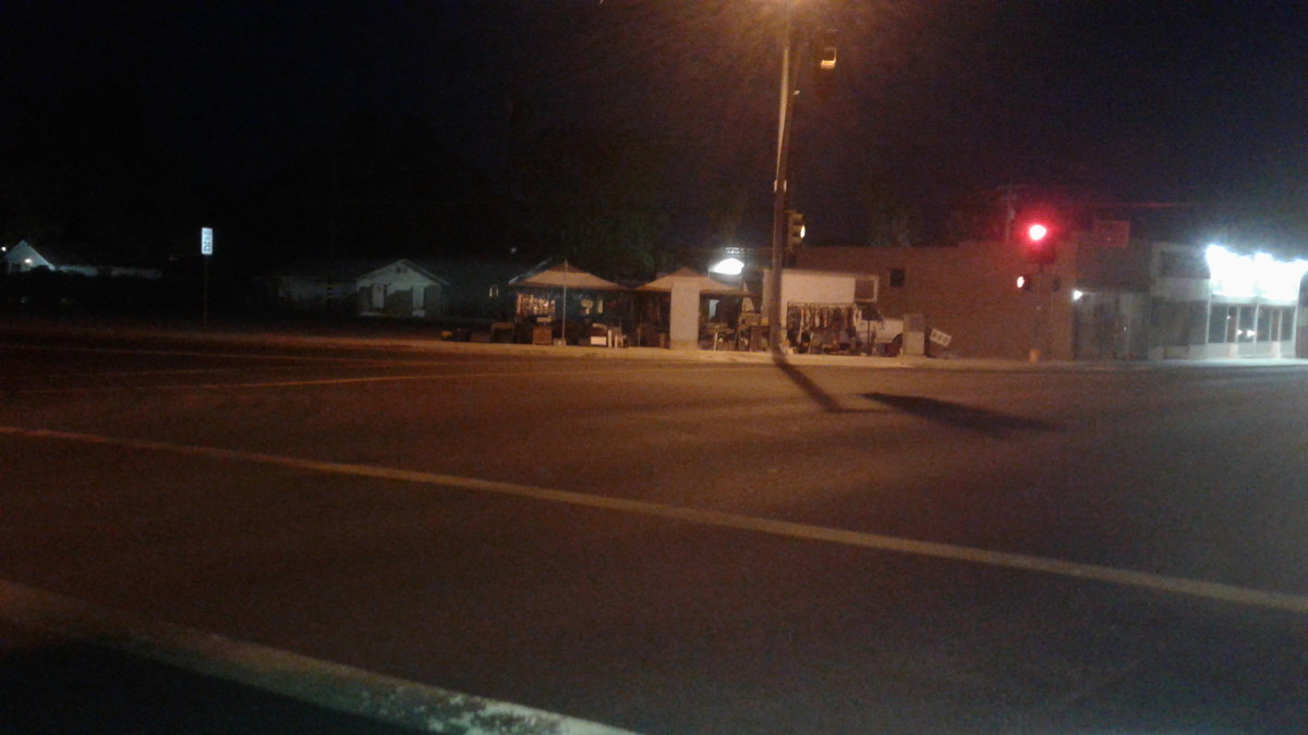 A vendor has established a night time yard sale on a busy street corner