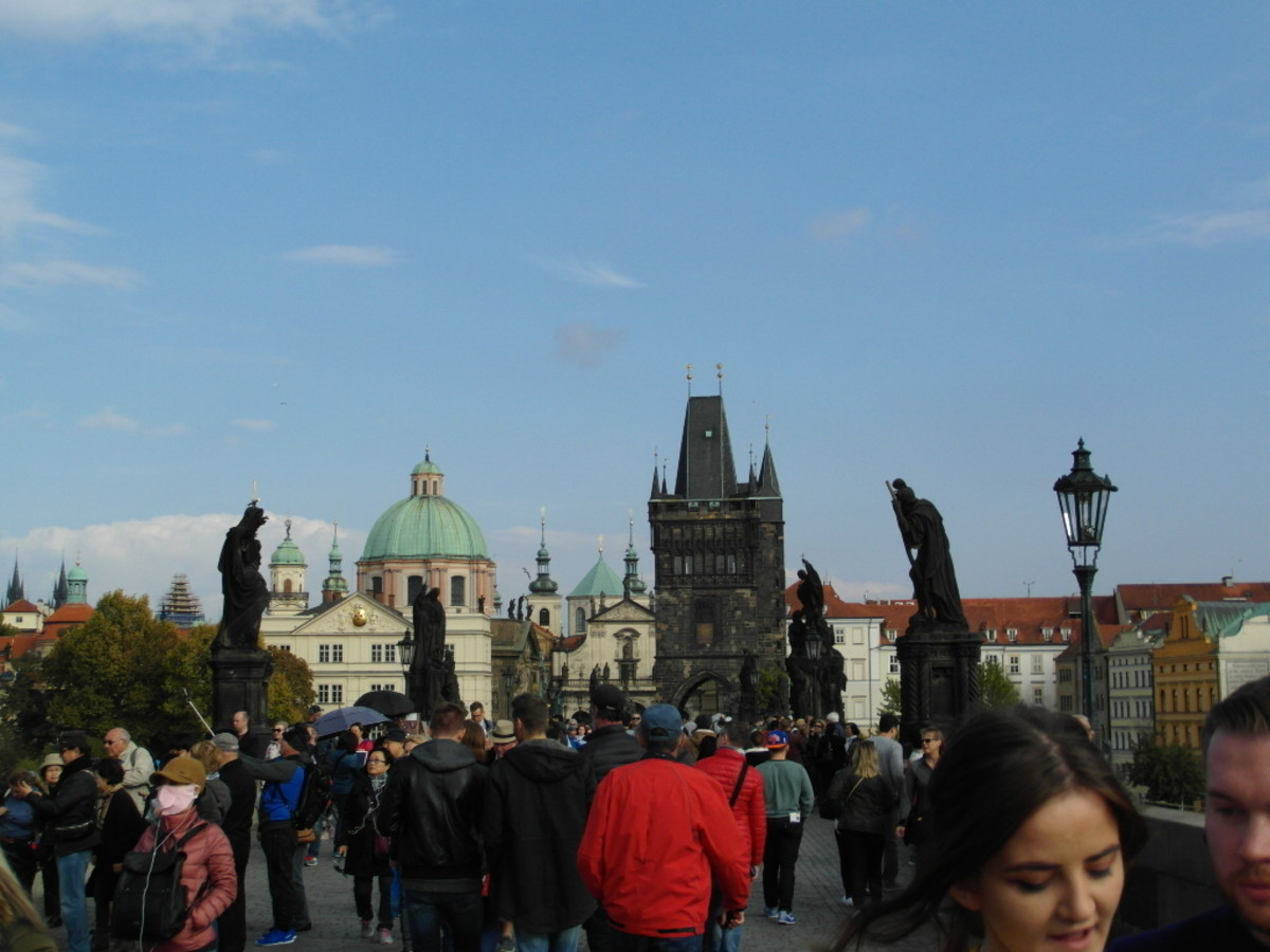 Crowds mingle with the statues on Charles Bridge.