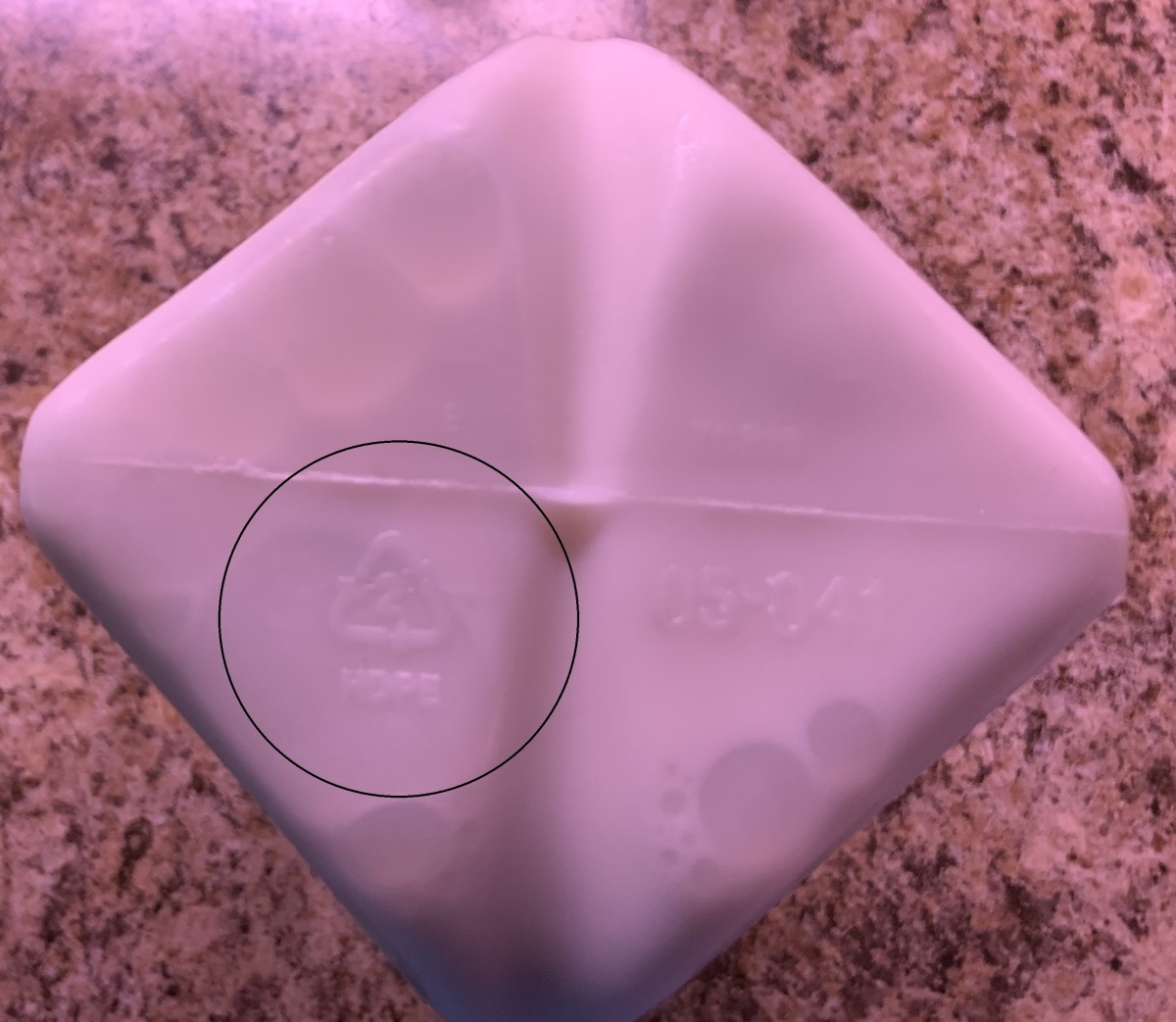 """Bottom of a half gallon of milk that has a """"2"""" inside a triangle with """"HDPE"""" next to the triangle. This is recyclable High density polyethylene plastic."""