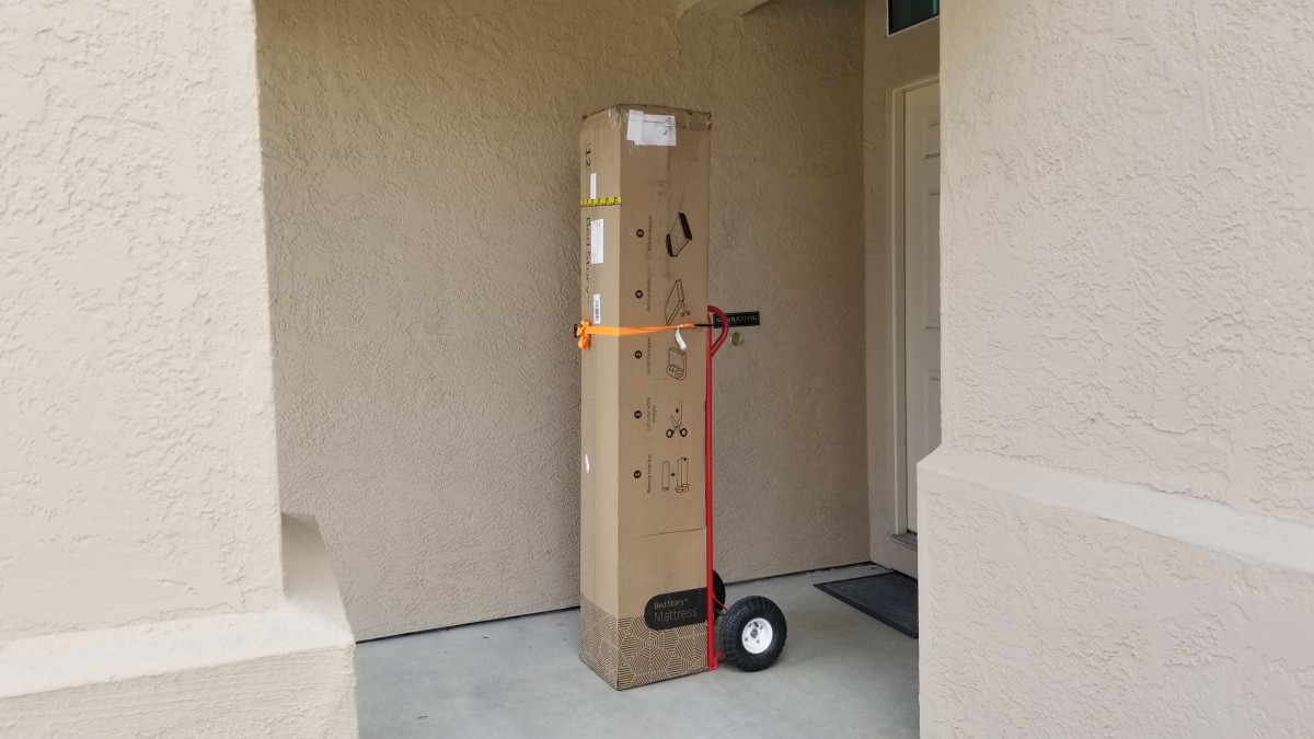 We used this red hand truck and a simple tie down to wheel the approximately 80 pound box to our second floor bedroom.