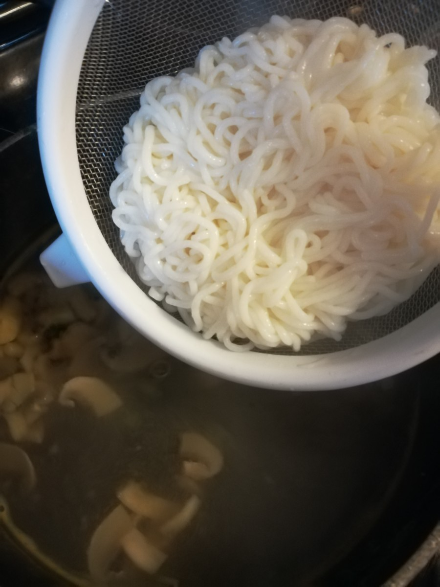 Adding the drained and rinsed tofu spaghetti noodles to the broth.