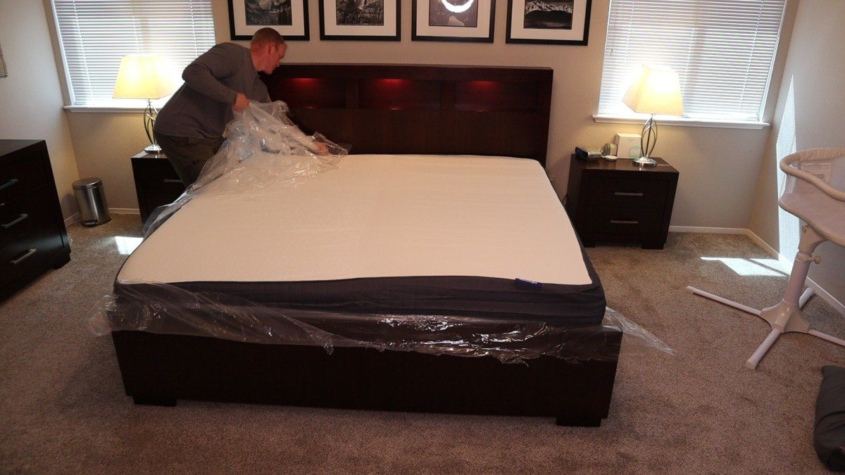 The inner layer of plastic is cut and the mattress starts to expand. My husband is removing the last of the plastic.