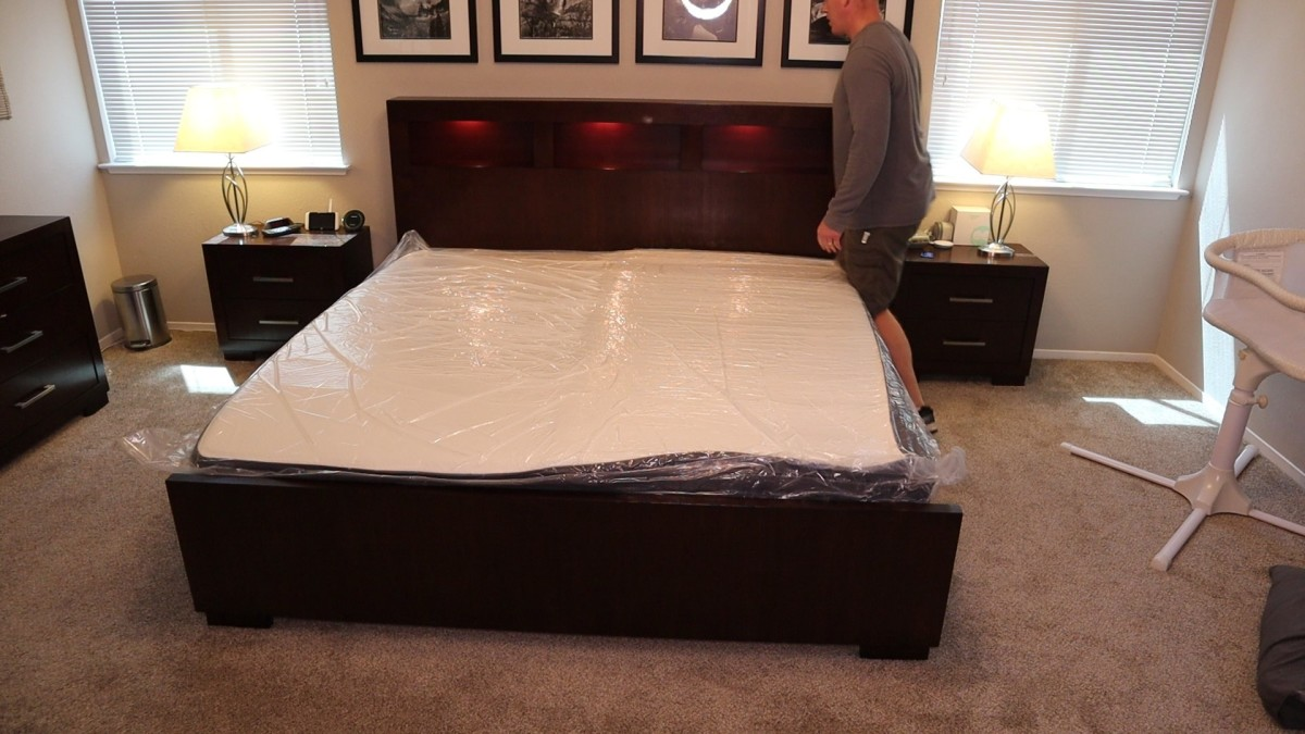 The mattress is unrolled and placed into the correct position after the outer layer of plastic is cut and removed. The inner plastic remains keeping the mattress compressed.