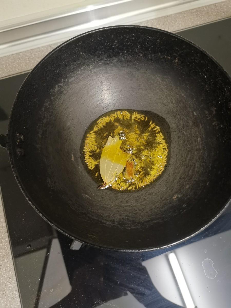 Add oil, cumin seeds, bay leaf, crushed cinnamon, cloves, and cardamom. Stir till it turns aromatic