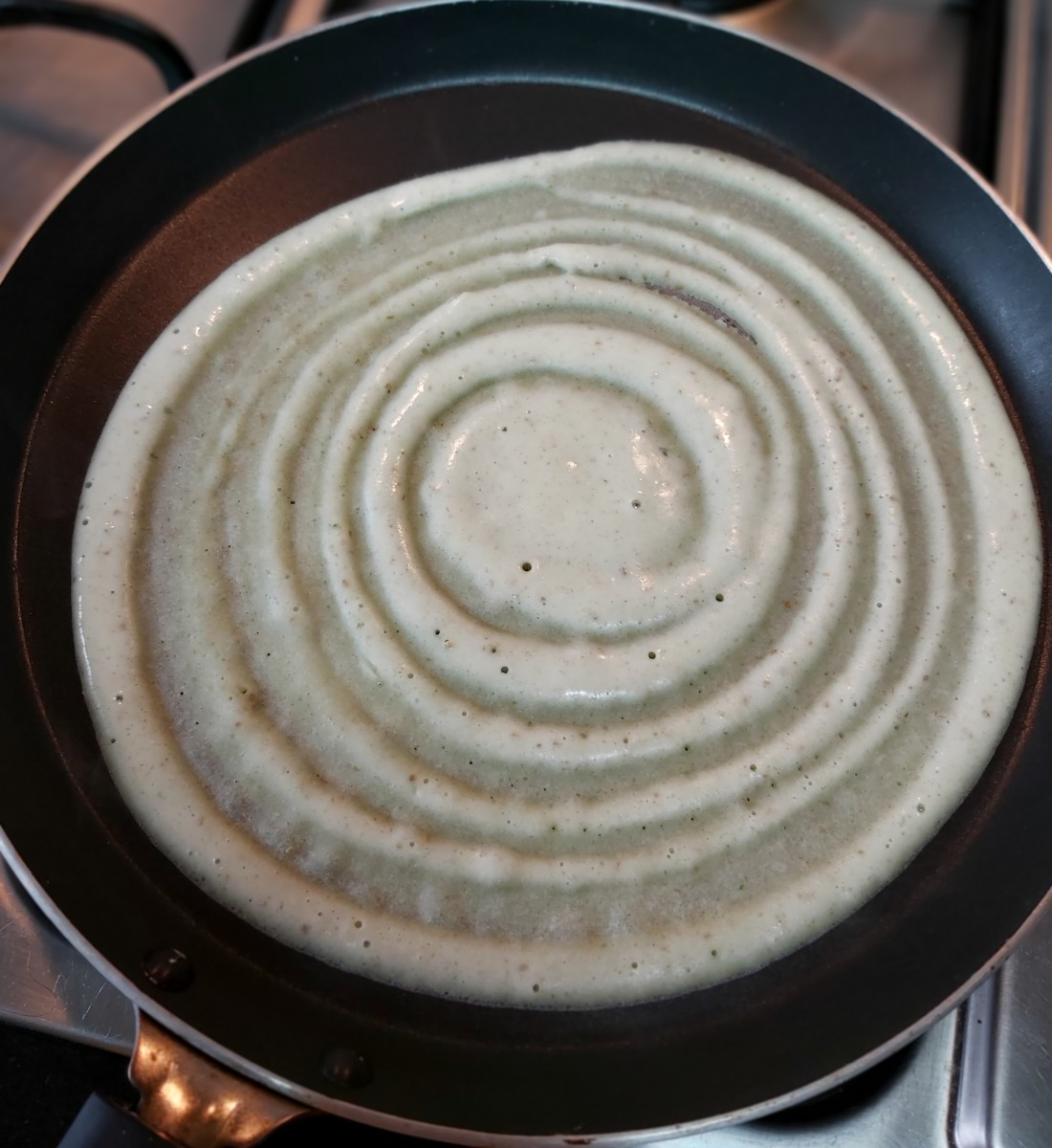 Pour a ladleful of batter in the center of the pan. Gently spread the batter in a circular motion, forming a thin dosa.