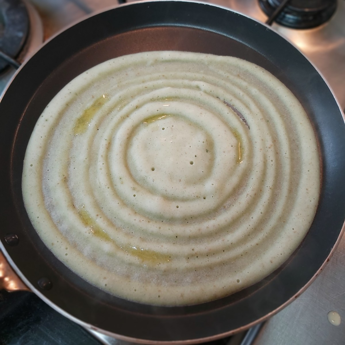 Smear a few drops of ghee on the dosa. Cover and cook on medium to low heat for about 1 minute or till it has cooked properly.