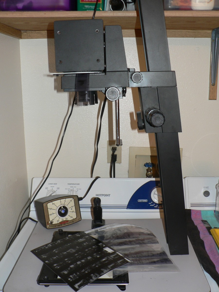 Darkroom Basics - Enlarger with negatives in negative holder, timer, and contact sheet.
