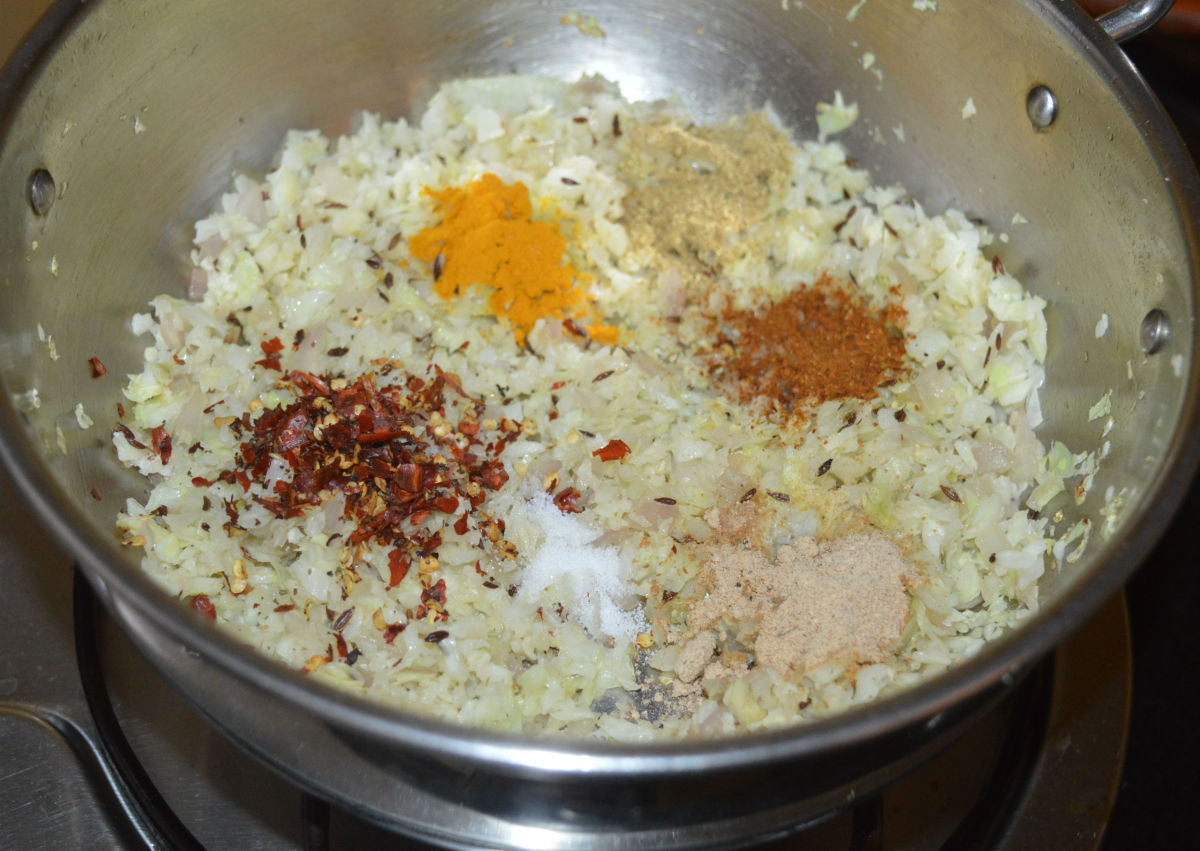Step two: Reduce the heat and add all the spices, such as turmeric powder, chili flakes, coriander powder, dry mango powder, garam masala powder, and remaining salt.