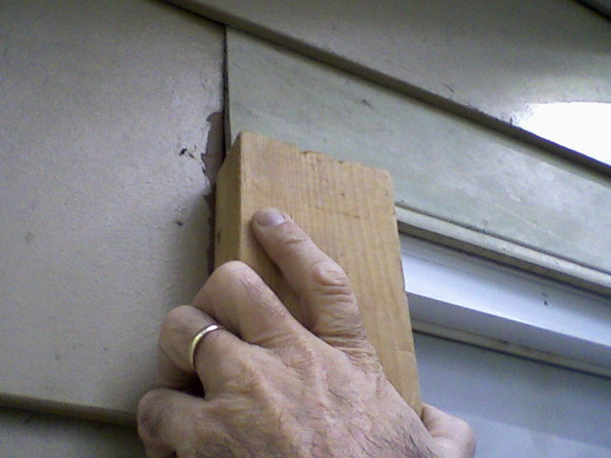 Using a scrap wood block to nudge the new siding into place.