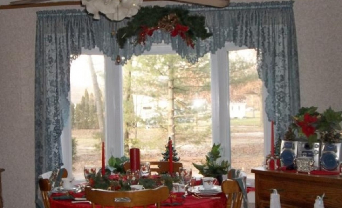 A simple swag centered over the curtain with no wall items to take away from the view.   The outside appears to be drawn into the room making it an elegant but cozy environment on a cold winter's day.