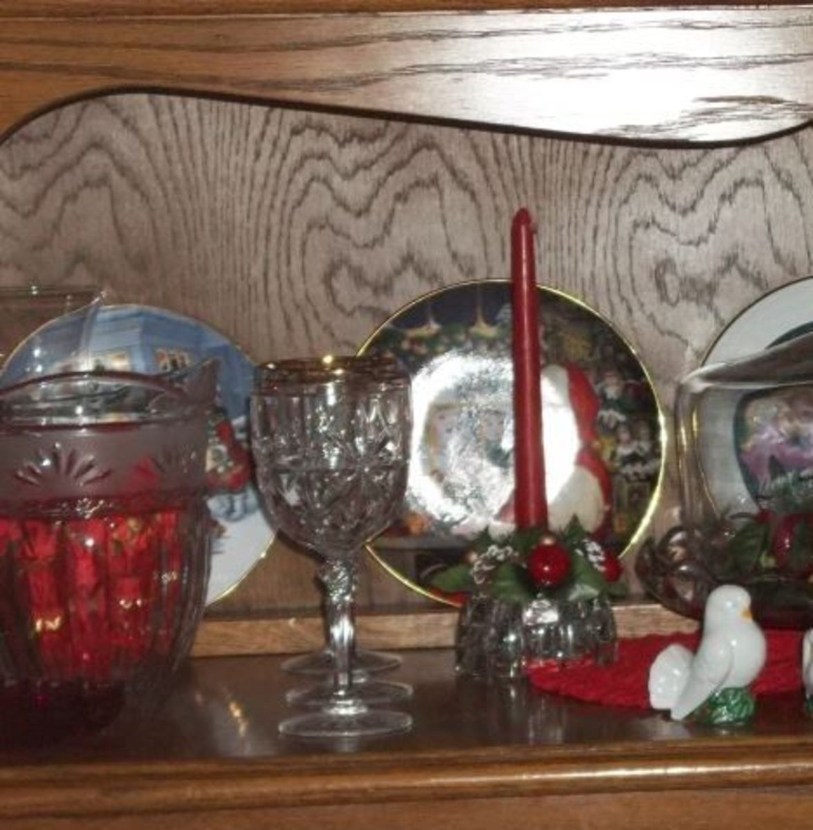 Colored balls in a crystal ice bucket and collector's Christmas plates make their own little Christmas scene.  The wood is highlighted by natural light.  A small puffed placemat does not overwhelm the space or take away from the attractive pieces.