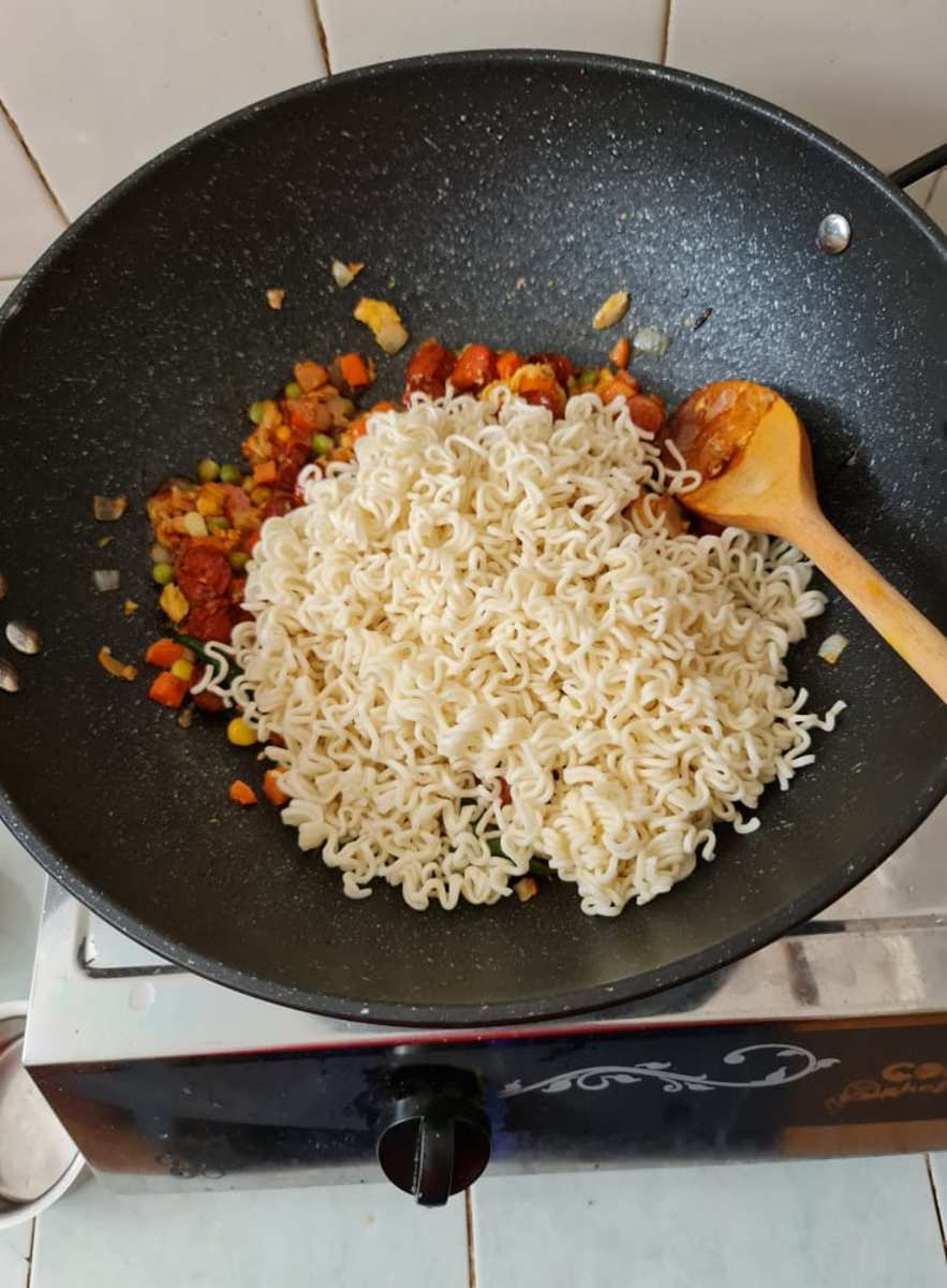 Add the cooked noodles to the wok.