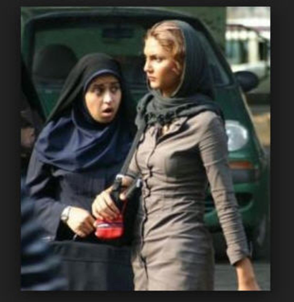 Two Iranian women comply to dress code. The taller one would be a target, however.