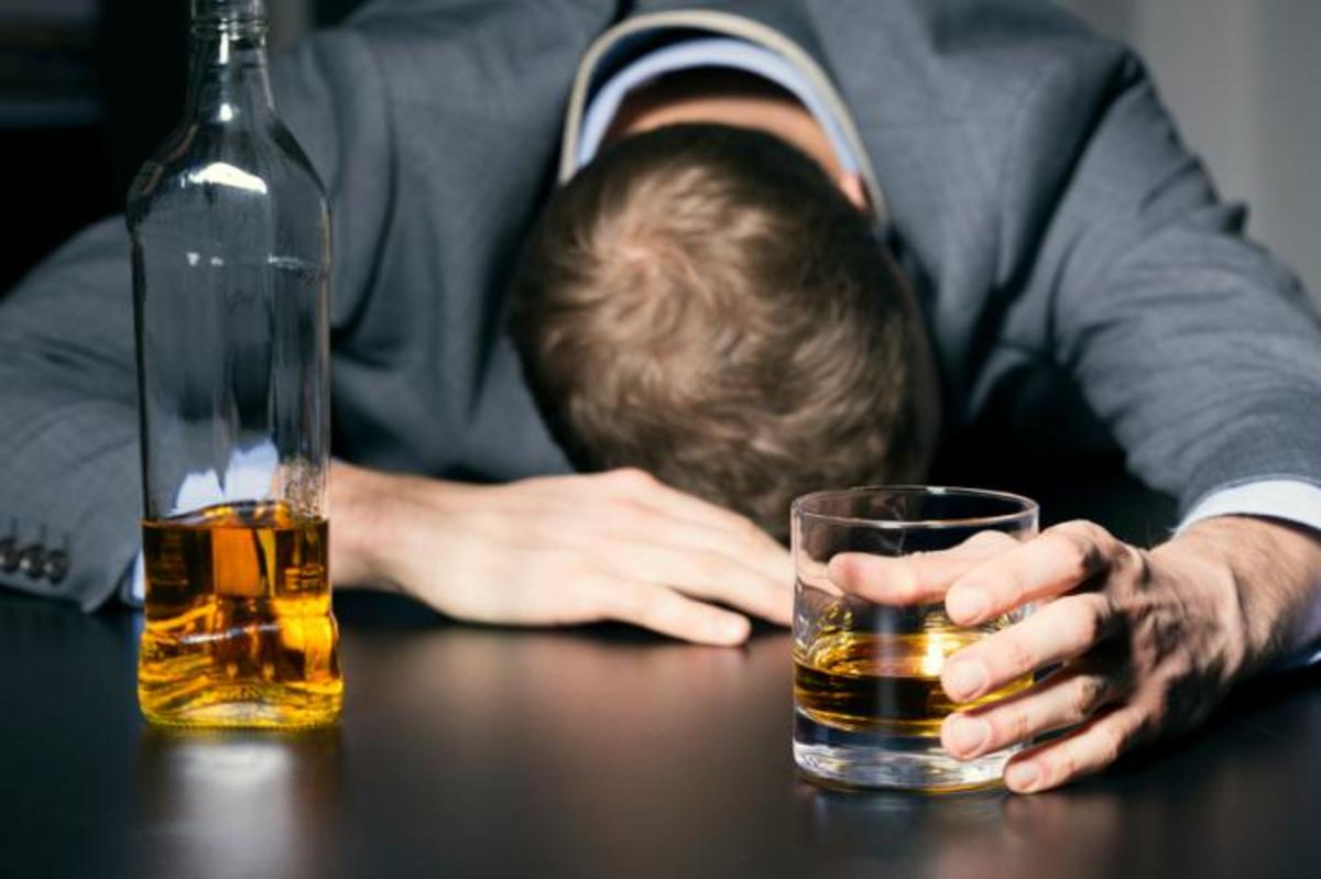 The image above shows a man sinking his sorrows into alcohol.