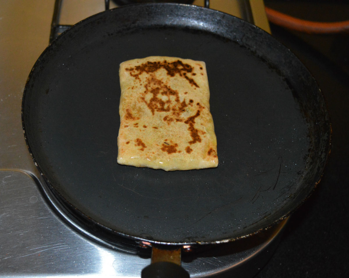 Step five: Heat a pan or griddle. Place a raw paratha in the center. Add a few drops of oil or melted ghee on top. Let the bottom side become golden brown. Flip it. Add oil or ghee on the top. Allow the other side to get golden brown spots, as well.