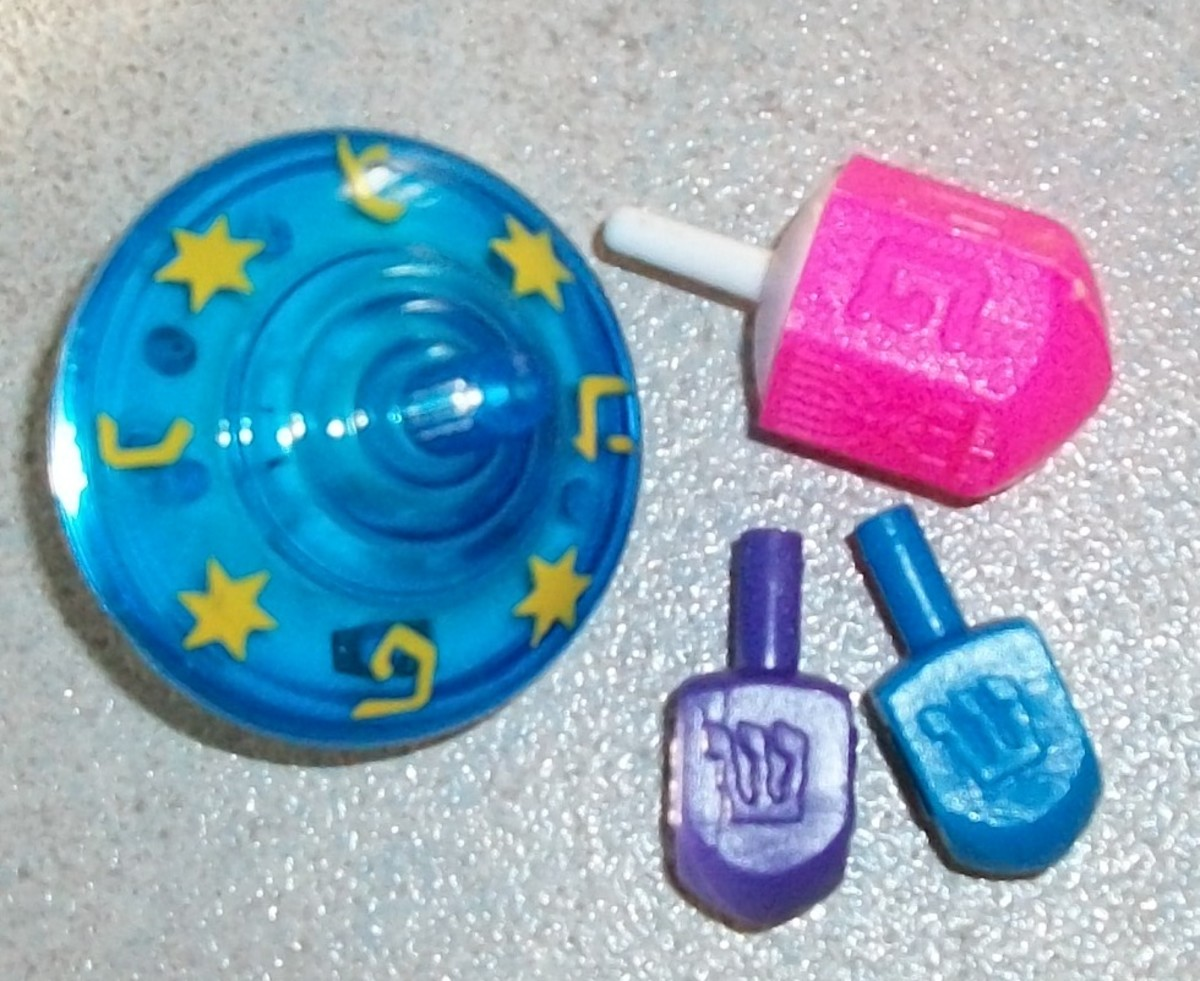 """Round musical sevivon and pink sevivon are from Israel. You see letter """"Pey"""". Purple and blue dreidels have letter """"shin"""", we got them in America"""