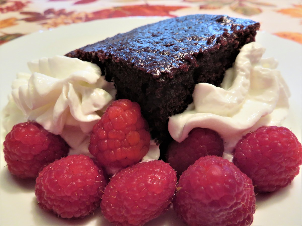 Piece of chocolate mayonnaise cake served with ReddiWip and fresh raspberries