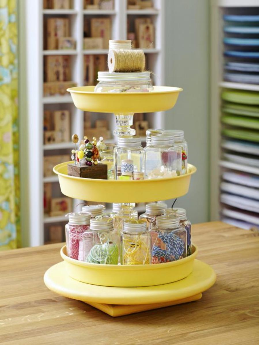 Use a lazy susan and some cake pans to create your own tired storage unit, Spray paint and glue the pans.Inexpensive glass candle holders are used in between the layers, Many of these can be found at your local dollar store or thrift shops.
